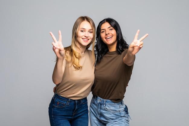 Retrato de duas amigas mostrando sinal de dois dedos na parede cinza e olhando para a frente