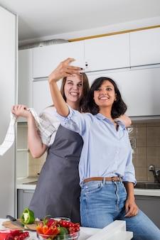 Retrato de duas amigas tomando selfie no celular na cozinha