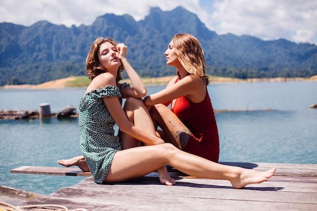 Retrato de duas amigas turísticas em vestidos de verão na viagem de férias ao redor do lago khao sok da tailândia com bela vista para a montanha.