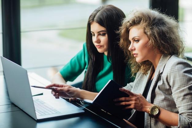 Retrato de duas belas e elegantes jovens, meninas sentadas em um restaurante à mesa, conversando e usando um laptop enquanto têm um intervalo.