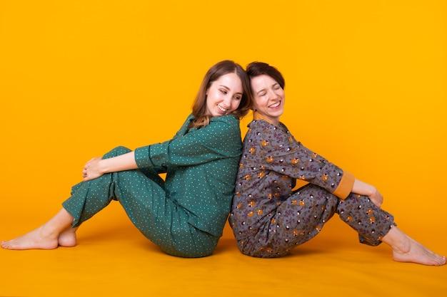 Retrato de duas belas garotas de pijama colorido, se divertindo durante a festa do pijama isolada sobre a parede amarela. festa do pijama e conceito de despedida de solteiro