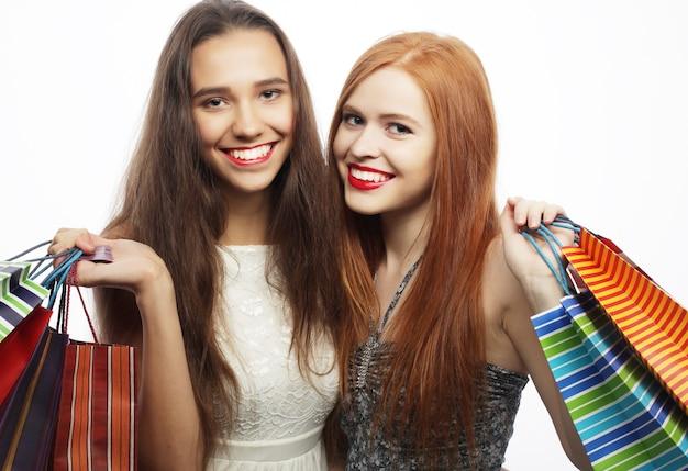 Retrato de duas belas moças com sacolas de compras