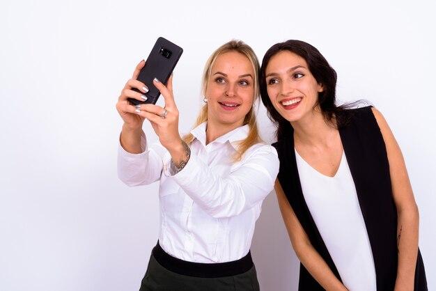 Retrato de duas belas mulheres de negócios juntas contra uma parede branca
