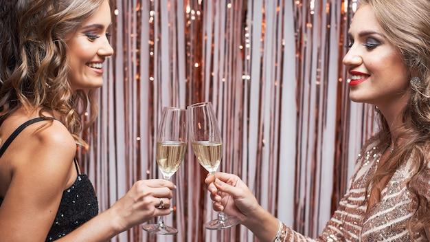 Retrato de duas belas mulheres elegantes tilintar de copos de champanhe.
