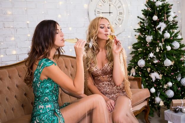 Retrato de duas belas mulheres em vestidos longos bebendo champanhe na sala de estar com árvore de natal decorada