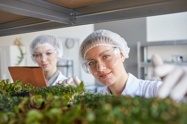 Retrato de duas cientistas sorrindo examinando amostras de plantas enquanto trabalhava no laboratório de biotecnologia, copie o espaço