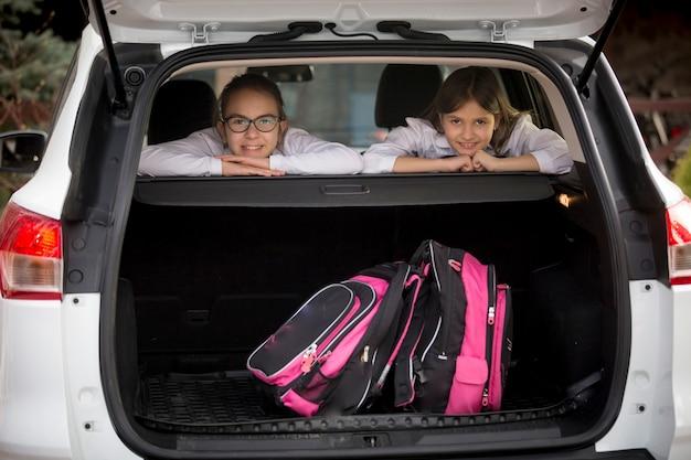Retrato de duas colegiais sorridentes olhando pelo porta-malas aberto
