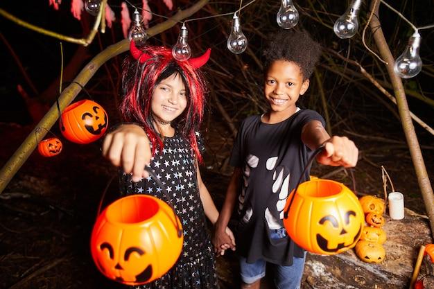 Retrato de duas crianças felizes em fantasias segurando cestas e esperando por guloseimas durante a festa de halloween