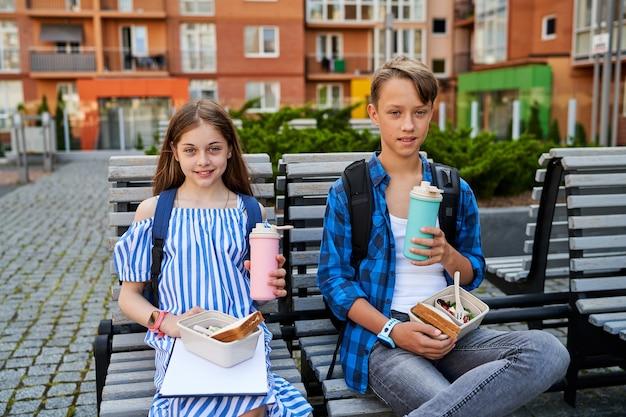 Retrato de duas crianças, menina e menino, perto da escola, comendo sanduíche e bebe chá da lancheira e da garrafa térmica.