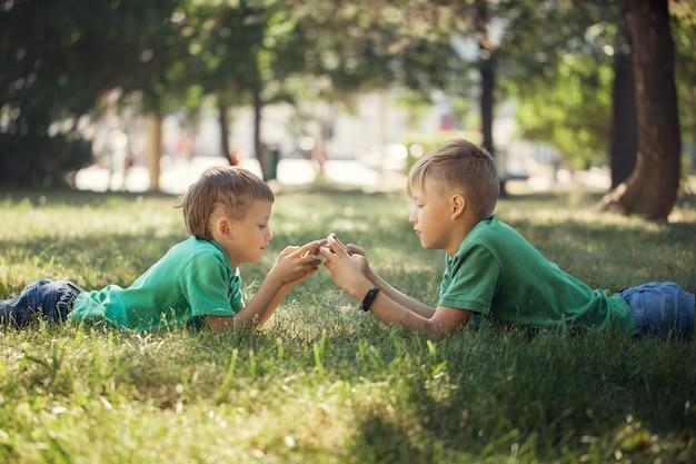 Retrato de duas crianças que encontram-se na grama verde e que jogam no telefone móvel.