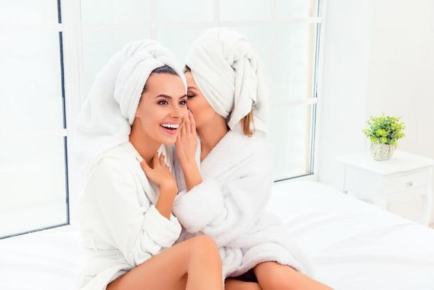 Retrato de duas fofoqueiras felizes em roupões de banho conversando em particular