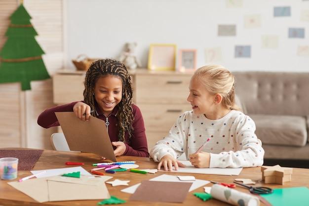 Retrato de duas garotas alegres trabalhando juntas e pintando enquanto estão sentadas em uma mesa em uma sala de jogos decorada