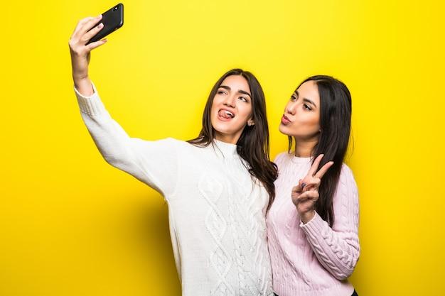 Retrato de duas garotas alegres, vestidas com suéteres, em pé e tirando uma selfie isolada na parede amarela