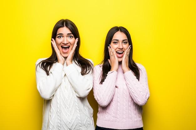 Retrato de duas garotas animadas, vestidas com suéteres, gritando, isoladas na parede amarela