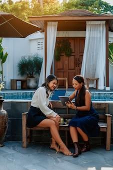 Retrato de duas garotas asiáticas com tablet e coquetéis que sentado em um banco e discutindo algo do lado de fora.