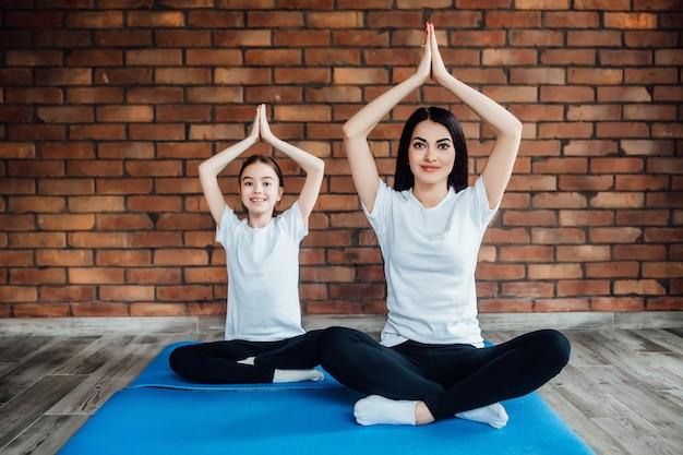 Retrato de duas garotas atraentes malhando em casa, fazendo exercícios de ioga na esteira azul, sentado na easy, na esteira azul.