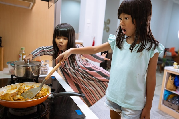 Retrato de duas garotinhas asiáticas cozinhando na cozinha