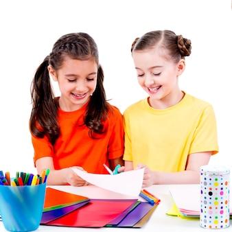 Retrato de duas garotinhas fofas em uma t-shirt colorida cortada em papelão de tesoura - isolado no branco