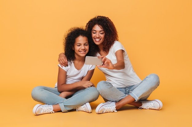 Retrato de duas irmãs afro-americanas alegres tomando selfie com smartphone
