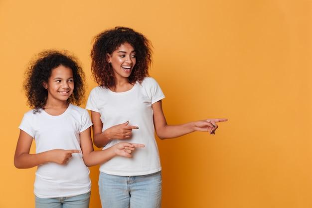 Retrato de duas irmãs afro-americanas felizes apontando