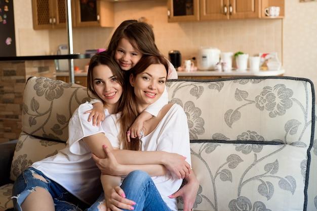 Retrato de duas irmãs e uma menina sentada no sofá, sorrindo.