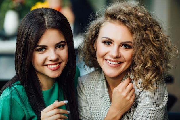 Retrato de duas irmãs jovens e fofas sorrindo, passou o fim de semana engraçado no café juntos.