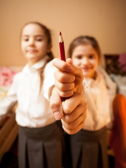 Retrato de duas irmãzinhas segurando um lápis vermelho