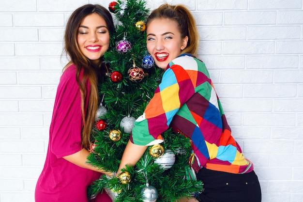 Retrato de duas jovens abraçando uma árvore de natal