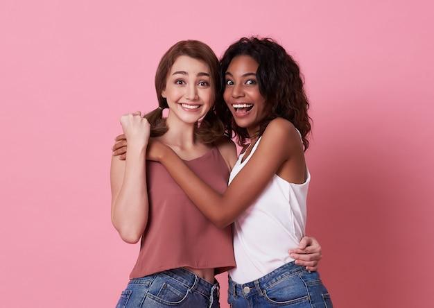 Retrato de duas jovens feliz e abraço juntos sobre rosa.