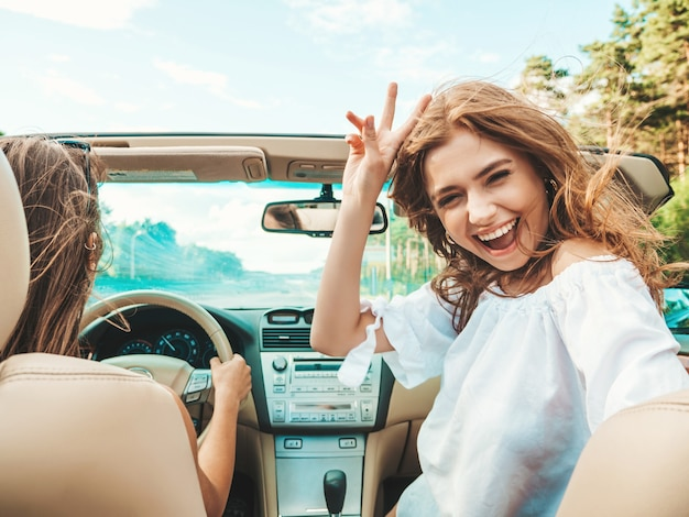 Retrato de duas jovens lindas e sorridentes garotas hippie em um carro conversível