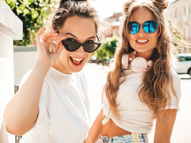 Retrato de duas jovens lindas sorrindo hipster femininas com roupas da moda de verão branco