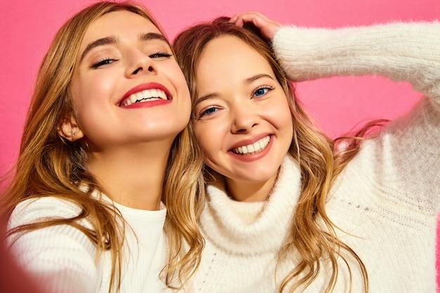 Retrato de duas jovens loiras sorridentes elegantes