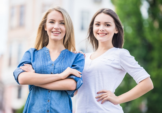 Retrato de duas jovens mulheres bonitas que olham a câmera.