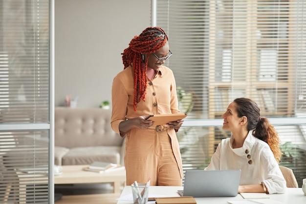 Retrato de duas jovens sorridentes discutindo projeto enquanto trabalhavam juntas no escritório, copie o espaço