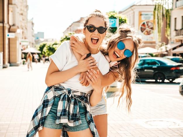 Retrato de duas lindas garotas hippie sorridentes com roupas da moda de verão camiseta branca Foto gratuita