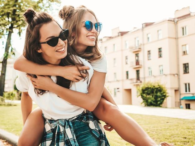 Retrato de duas lindas garotas hippie sorridentes com roupas da moda de verão camiseta branca