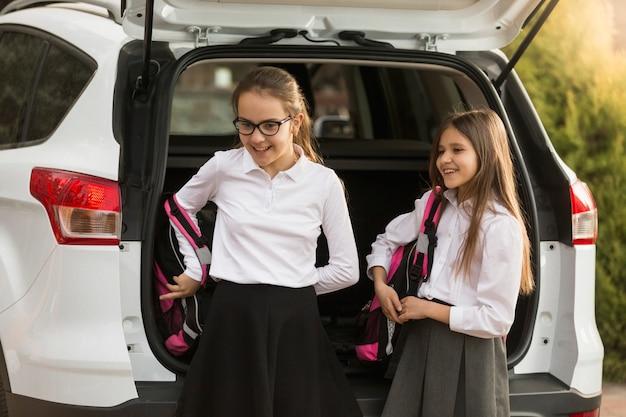 Retrato de duas lindas garotas tirando mochilas escolares do porta-malas do carro
