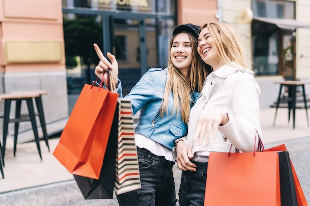 Retrato de duas loiras no meio de uma rua fazendo compras, uma delas aponta para as lojas de desconto