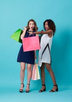 Retrato de duas mão jovem animado segurando a sacola de compras e com o dedo apontando