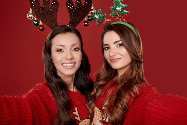 Retrato de duas melhores amigas malucas em suéteres de inverno aconchegantes da moda com atributos de natal tirando selfie na parede vermelha