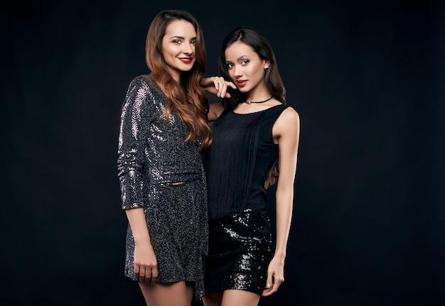 Retrato de duas melhores amigas malucas em vestidos de moda posando
