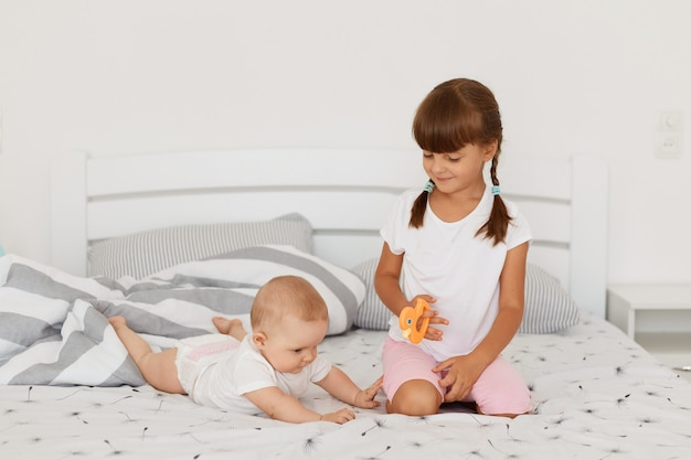 Retrato de duas menina vestindo camisetas brancas, posando em um quarto claro na cama, brincando juntos, menina infantil deitada de bruços perto de sua irmã mais velha, crianças passando algum tempo juntos em casa.