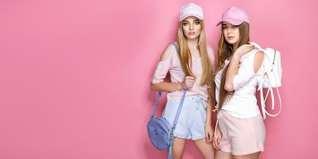 Retrato de duas meninas alegres animadas, vestidas com roupas coloridas brilhantes verão segurando sacos isolados.