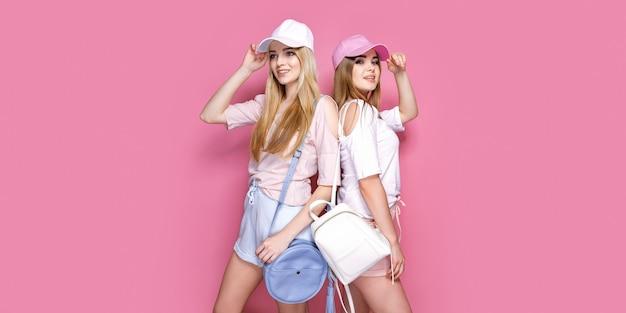 Retrato de duas meninas alegres animadas, vestidas com roupas coloridas brilhantes verão segurando sacos isolados. Foto Premium
