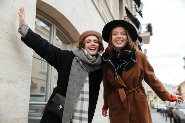 Retrato de duas meninas alegres, vestidas com roupas de outono andando