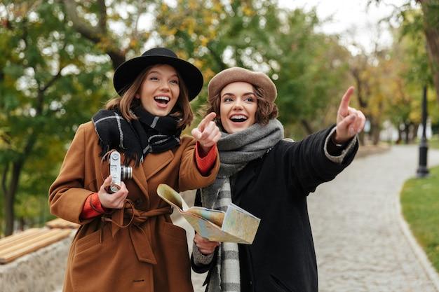 Retrato de duas meninas alegres, vestidas com roupas de outono
