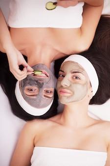 Retrato de duas meninas bonitas com creme facial em seus rostos olhando e deitado frente a frente no chão e sorrindo