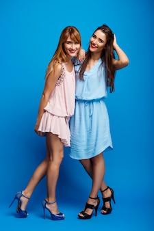 Retrato de duas meninas bonitas sobre parede azul
