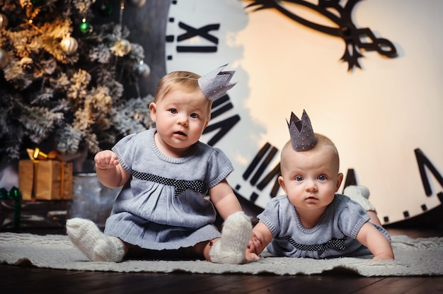 Retrato de duas meninas com coroas nas cabeças no interior de uma casa ao lado de árvores de natal.