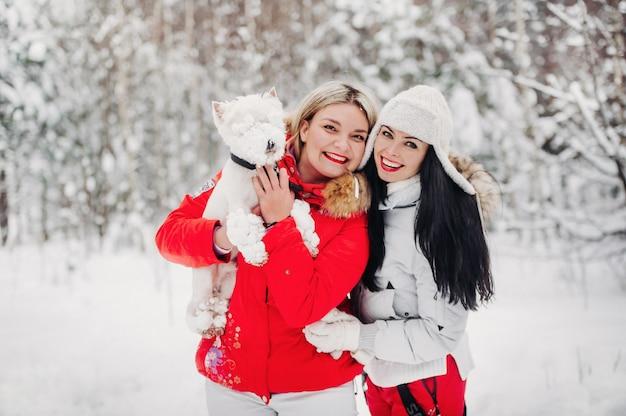 Retrato de duas meninas com um cachorro em uma floresta fria de inverno. uma garota segura um cachorro nos braços em uma floresta de neve no inverno